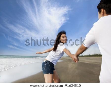 happy asian couple running on the beach - stock photo