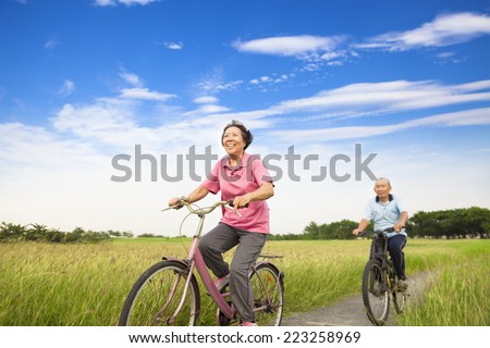 Happy Asian elderly seniors couple biking in farm with blue sky background - stock photo