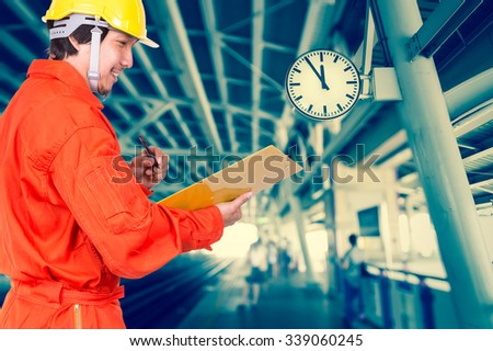 Happy Asian engineers writing the note pad on abstract Blurred photo of sky train, transportation industrial concept - stock photo