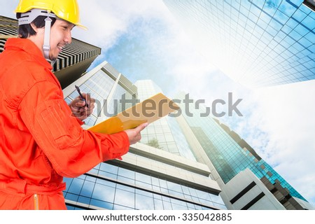 Happy Asian engineers writing the note pad on Modern business building glass of skyscrapers, Business concept of architecture industrial concept - stock photo