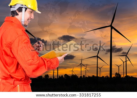 Happy Asian engineers writing the note pad on Wind turbine power generator with world map at twilight time, industrial concept, Elements of this image furnished by NASA - stock photo