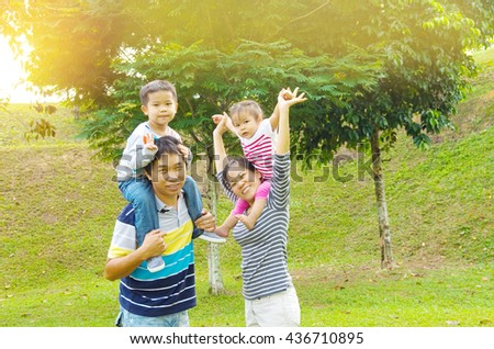 Happy Asian Family enjoying family time together in the park - stock photo