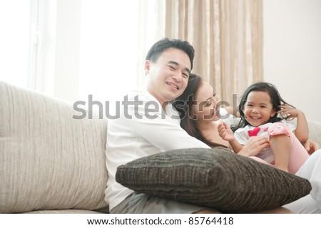 Happy Asian Family enjoying time together sitting on sofa - stock photo