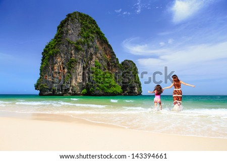 Happy asian family have fun on beach run and jump at beach - stock photo