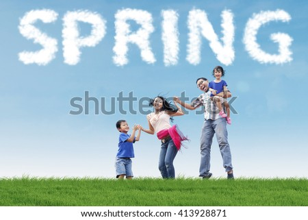 Happy asian family holding hands and jumping together on the field under a spring cloud