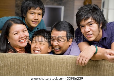 Happy Asian family in the living room gazing to camera.