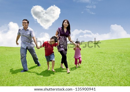 Happy asian family is having a stroll in the park under heart shape clouds