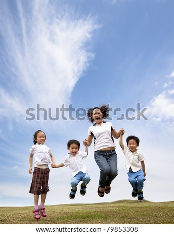 happy asian family  jumping on the grass field. mother and her children - stock photo