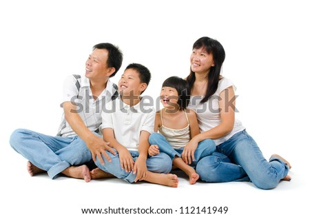 Happy Asian family looking at side, sitting on white background - stock photo