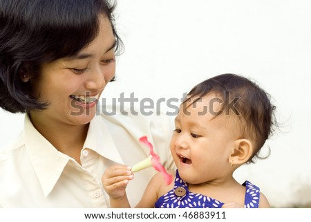 happy asian family: mother and baby playing together outdoor - stock photo