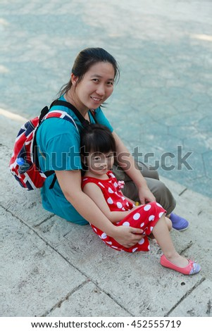 Happy asian family, mother and lovely daughter smiling and looking at camera. Playful child and parent have fun and relaxing outdoors in the day time, travel on vacation. Positive human emotion. - stock photo