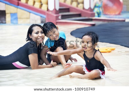 Happy asian family of three having fun at swimming pool - stock photo
