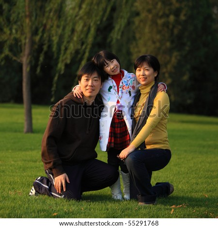 Happy Asian family on the grass in autumn - stock photo