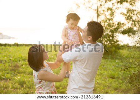Happy Asian family playing in meadow during summer sunset, outdoors shot. - stock photo