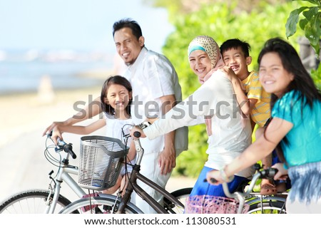 Happy asian family riding bikes in the beautiful morning at the beach