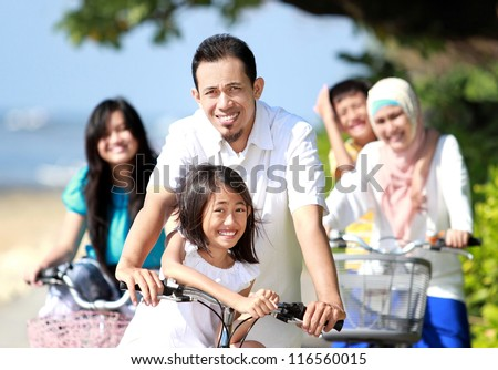 Happy asian family riding bikes in the beautiful morning at the beach - stock photo