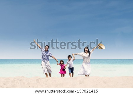 Happy Asian family running at beach - stock photo