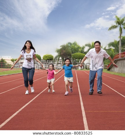 happy asian family running together on the Stadium track - stock photo