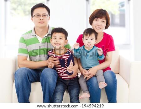 happy asian  family sitting on a white leather sofa  - stock photo