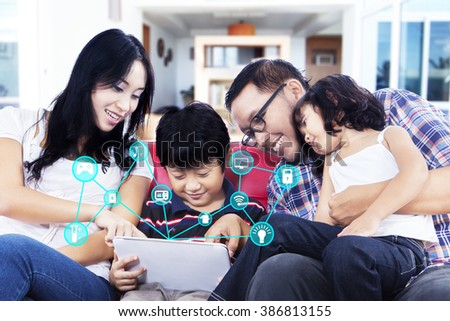 Happy Asian family sitting on the sofa while using a digital tablet with smart home system controller - stock photo