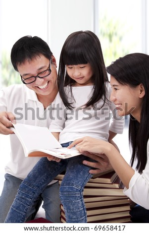 Happy asian family studying together. Parent helping daughter  reading book - stock photo