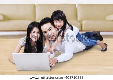 Happy Asian family using a laptop computer while lying on the floor at home and smiling at the camera - stock photo