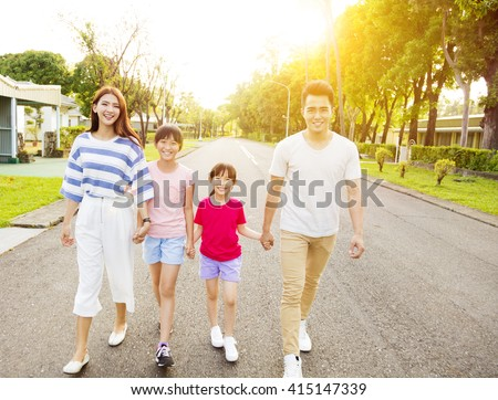 happy asian family walking on the street - stock photo