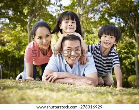 happy asian family with two children taking a family photo outdoors in a park. - stock photo