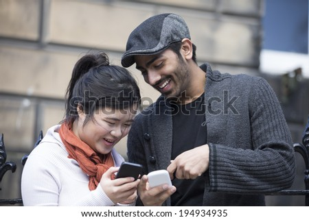 Happy Asian friends using mobile phone outside in street. Young urban couple 'hanging out' in the city using tech. - stock photo