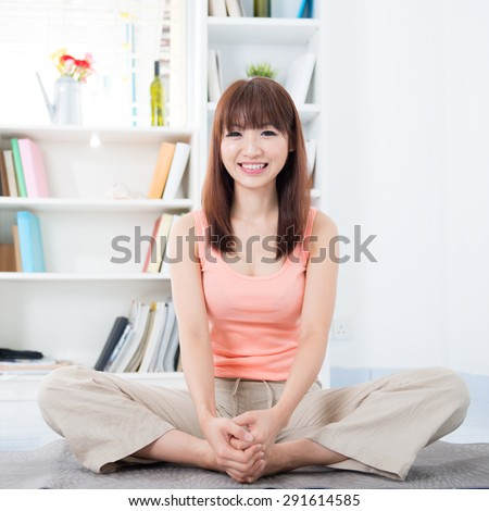 Happy Asian girl doing yoga in the morning. Young woman indoors living lifestyle at home.