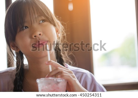 Happy Asian girl drinking ice strawberry smoothie in cafe