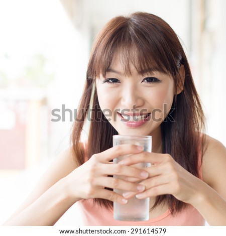 Happy Asian girl drinking mineral water at outdoor cafe. Young woman living lifestyle. - stock photo
