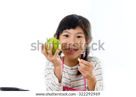 Happy Asian girl eating green apple, isolated on white.