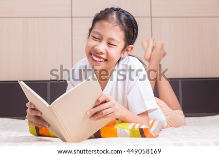 Happy Asian girl enjoying reading a book in her warm and cozy bed - stock photo