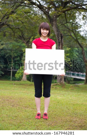 Happy Asian girl holding a white blank card at outdoor park - stock photo