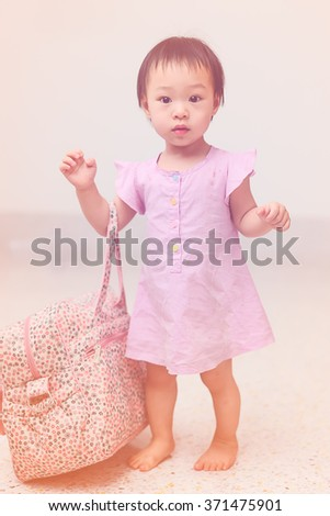 Happy Asian girl holding bag at home. - stock photo