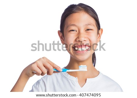 Happy asian girl holding toothbrush, looking and smiling at camera, isolated white background