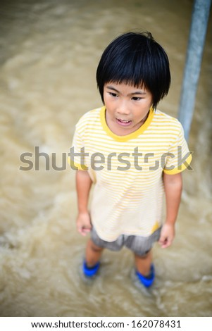Happy Asian girl in blue boots,flood disaster.