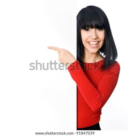 Happy asian girl pointing at a blank board
