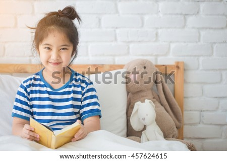 Happy Asian girl reading story book on the bed