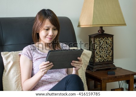 Happy asian girl sitting on bed using a tablet pc - stock photo