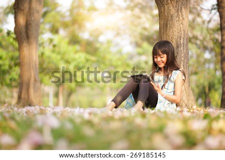 Happy asian girl sitting on grass with tablet computer in the park - stock photo