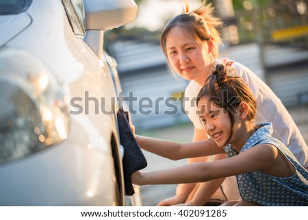 Happy Asian girl washing car with her mother at home - stock photo
