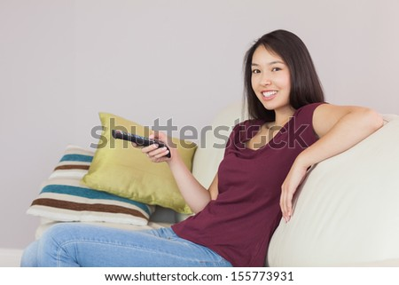Happy asian girl watching tv smiling at camera at home in the living room - stock photo