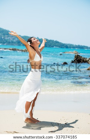 Happy asian girl with arms outstretched on the tropical beach