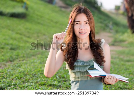 Happy Asian girl with her note outside on grass