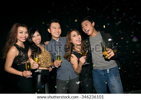 Happy Asian girls and guys at party in the club