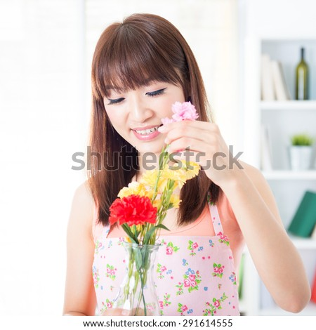 Happy Asian housewife with apron arranging flowers to vase. Young woman indoors living lifestyle at home. - stock photo