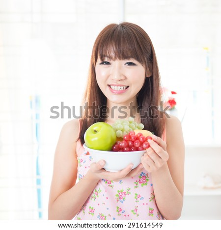 Happy Asian housewife with apron holding fresh fruits. Young woman indoors living lifestyle at home. - stock photo