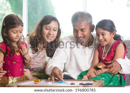 Happy Asian Indian family playing carrom game at home. Parents and children indoor lifestyle.
